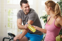 Woman on spin bike handing a water bottle to man on spin bike